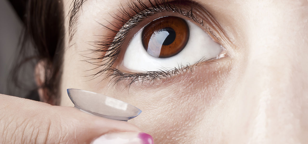close up of a woman's eye and a contact lens
