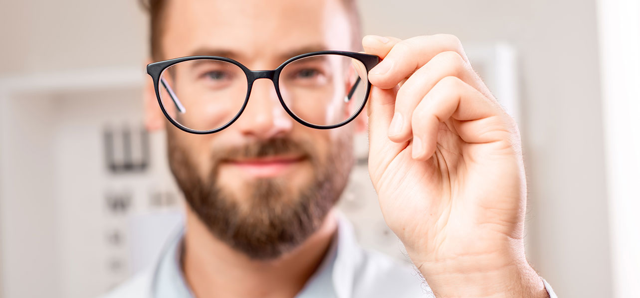 man holding up glasses to the camera