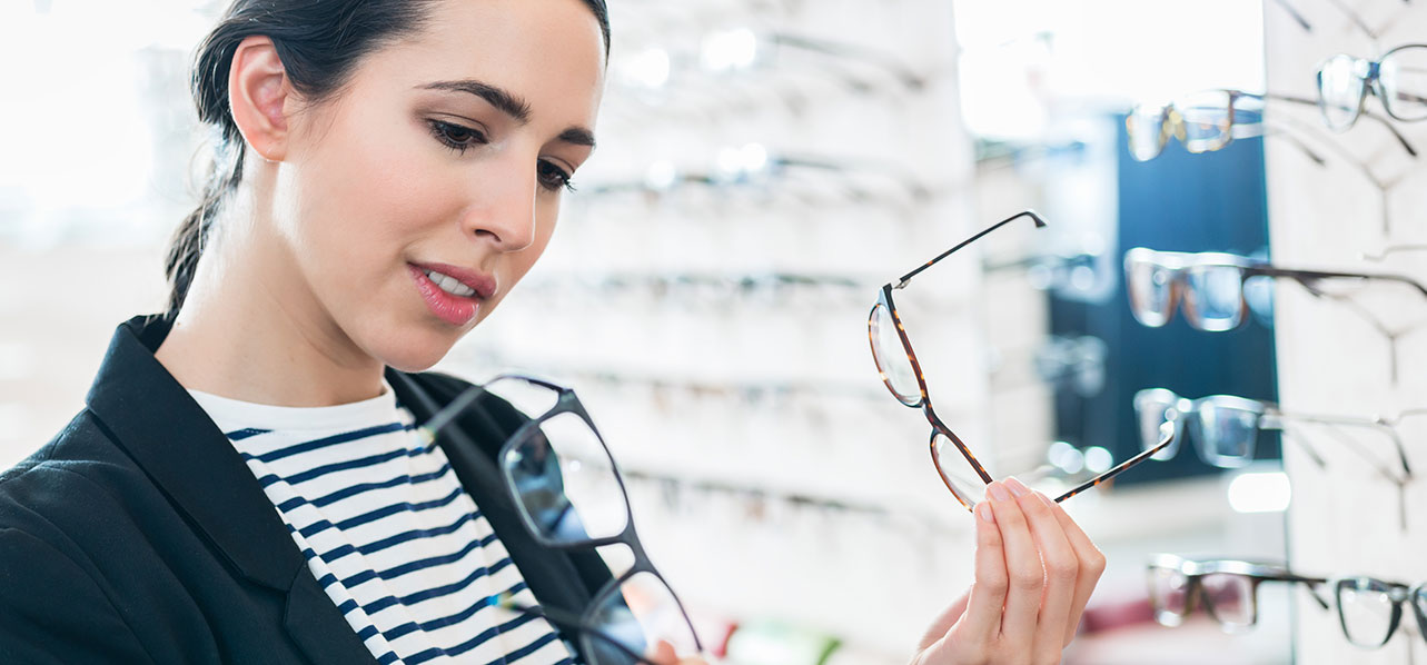 woman looking at glasses in optical shop