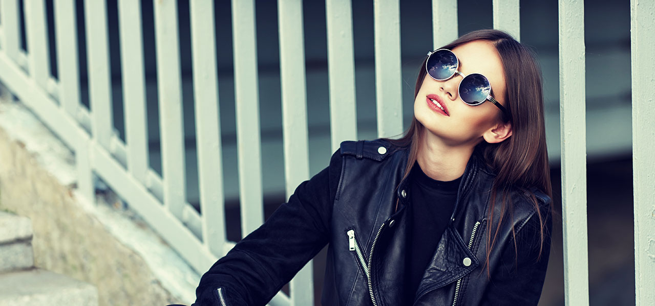 woman wearing leather jacket and cool sunglasses sitting on stairs